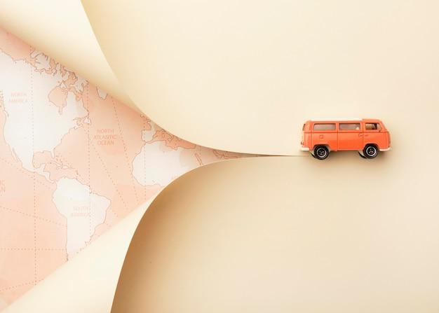 Reisconcept met wereldkaart en speelgoedbusje