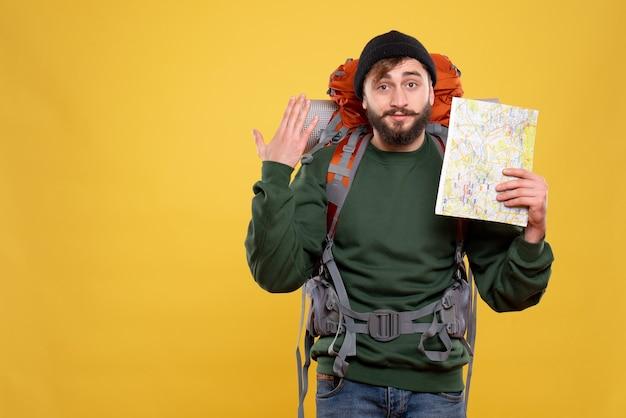 Reisconcept met zelfverzekerde jonge kerel met packpack en kaart te houden die op geel wordt weergegeven