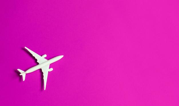 Reisconcept op roze achtergrond met exemplaarruimte. vliegtuigstuk speelgoed op roze kleurenachtergrond.