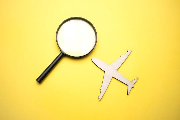 Reisconcept. vliegtuig, vergrootglas met een wereldbol op een gele achtergrond. bovenaanzicht. plat leggen