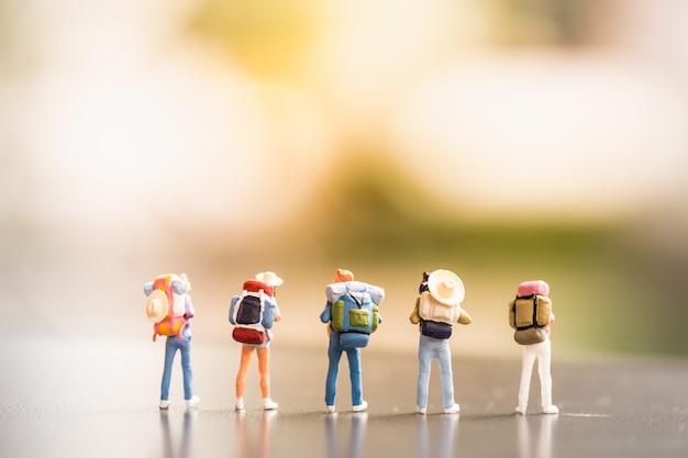 Reisconcepten. groep reizigers miniatuur minicijfers met rugzak en hoedentribune op grond