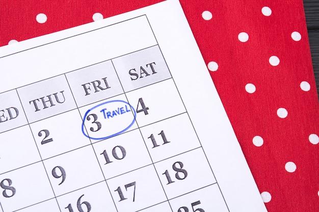 Reisdag omcirkeld in een papieren kalender vrijdag gemarkeerd in een kalender door een blauwe markering