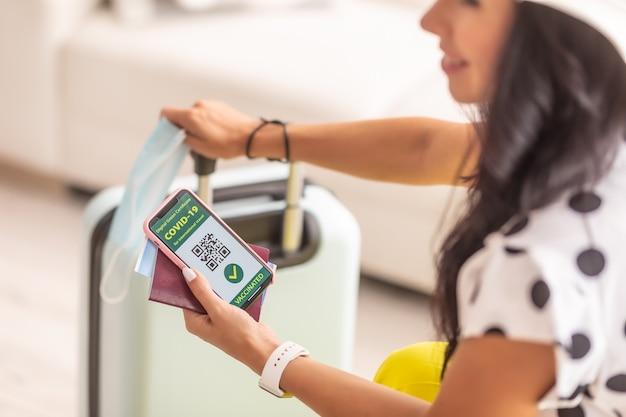 Reisdocumenten zoals paspoort, vliegticket en covid-19-pas met qr-code en gezichtsmasker in handen van reiziger.