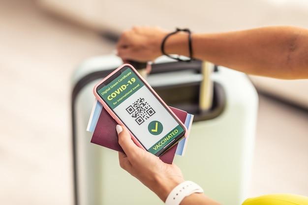 Reisdocumenten zoals paspoort, vliegticket en covid-19-pas met qr-code in handen van reiziger.