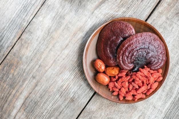 Reishi of lingzhi-paddenstoel, gojibes en rode jujube op een oud hout. bovenaanzicht