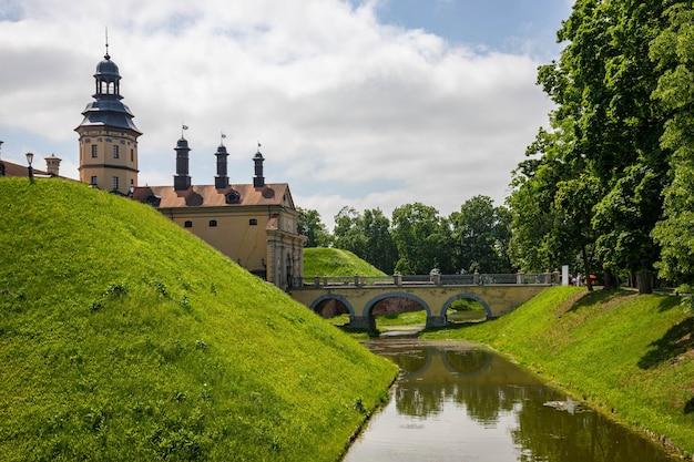 Reisideeën en concepten. nesvizh castle als een voorbeeld van wit-russisch historisch erfgoed van de radzivil-familie. ontsproten uit de gracht. horizontaal beeld