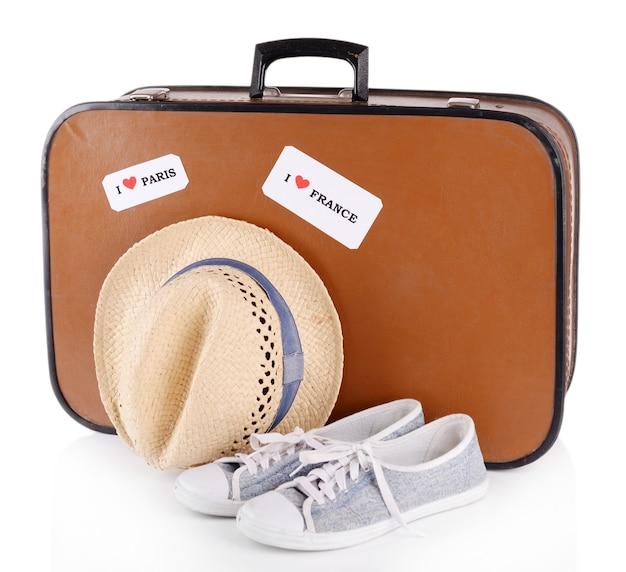 Reiskoffer, hoed en schoenen op wit