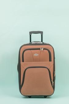 Reiskoffer met een handvat op een blauwe achtergrond.
