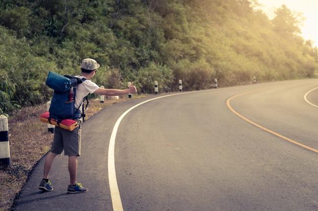 Reismens liftend. een lifter door de weg tijdens vakantiereis in bergen bij zonsondergang