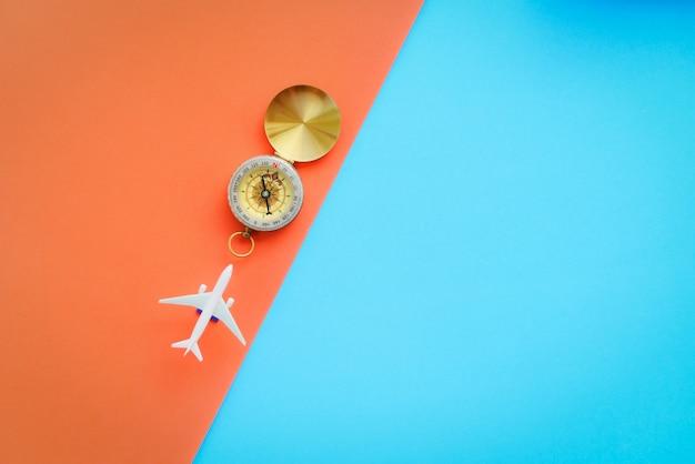 Reisoppervlakconcept vliegtuigreizigersvlieg met passagiersvliegtuig en kompas op blauw en oranje