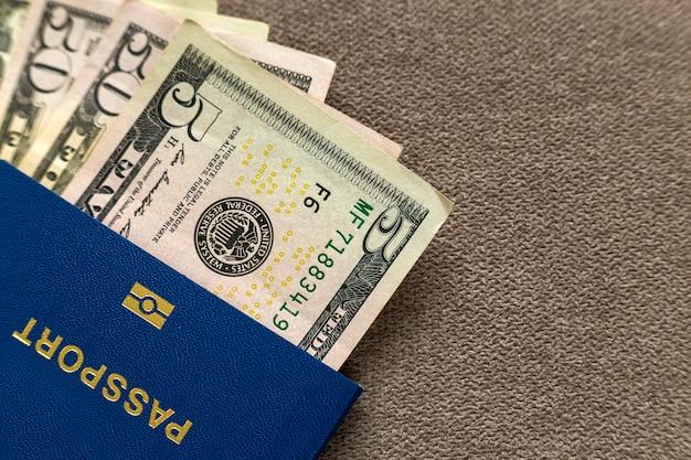 Reispaspoort en geld, de rekeningen van amerikaanse dollarsbankbiljetten. reizen en financieren problemen concept.
