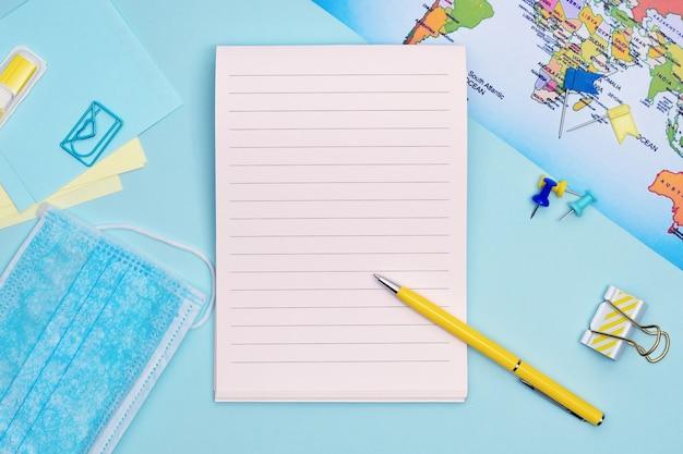 Reisplanning plat lag. planning van reizen na het einde van de quarantaine op blauwe achtergrond met kopie ruimte. stationaire items, medicijnmasker, kaart en notitieboekje bovenaanzicht.