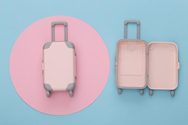 Reisplanning. twee stuk speelgoed reisbagage op blauw met roze cirkel. plat leggen