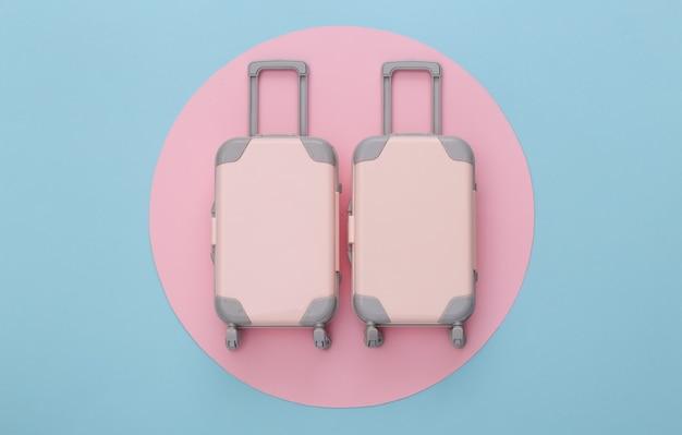 Reisplanning. twee stuk speelgoed reisbagage op blauw met roze cirkel