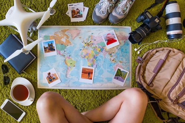 Reisset met camera, drone, rugzak en kaart met fotoherinneringen en plaatsen