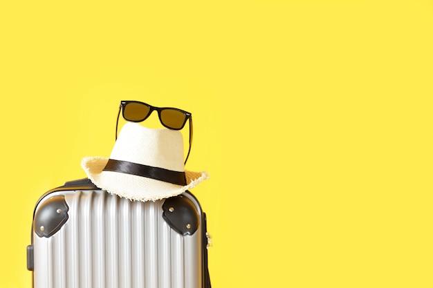 Reistas, bagage, strohoed en zonnebril op gele achtergrond met exemplaarruimte. koffer, hoed, zwarte zonnebril geïsoleerd op gele achtergrond. zomer reizen concept.