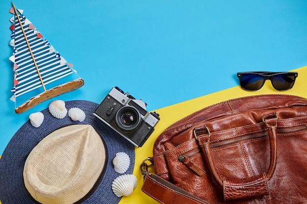 Reistas, zonnebril, handgemaakte zeilboot en camera op een gele en blauwe achtergrond. zomervakantie concept op zee reizen