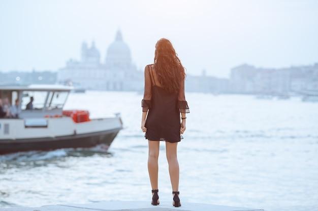 Reistoeristische vrouw op pier tegen prachtig uitzicht op venetiaanse chanal in venetië, italië.