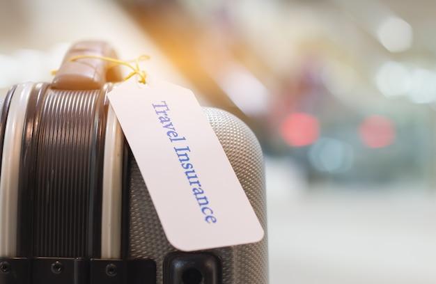 Reisverzekeringsetiket op kofferhouder met markering gebonden brieven plezierig uw reis op zak