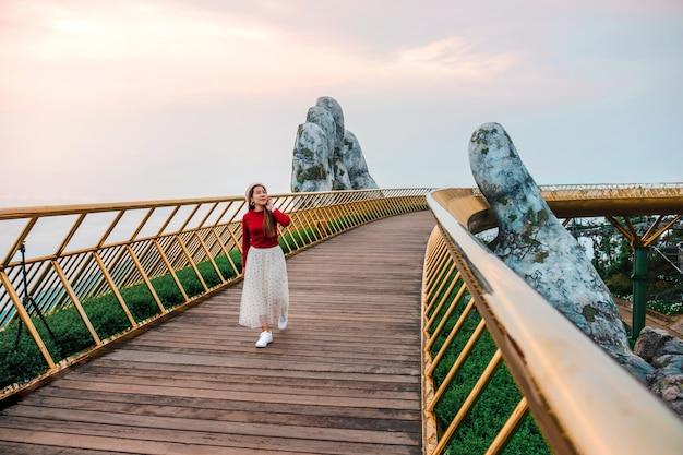 Reisvrouw bij gouden brug in ba na-heuvels, danang vietnam