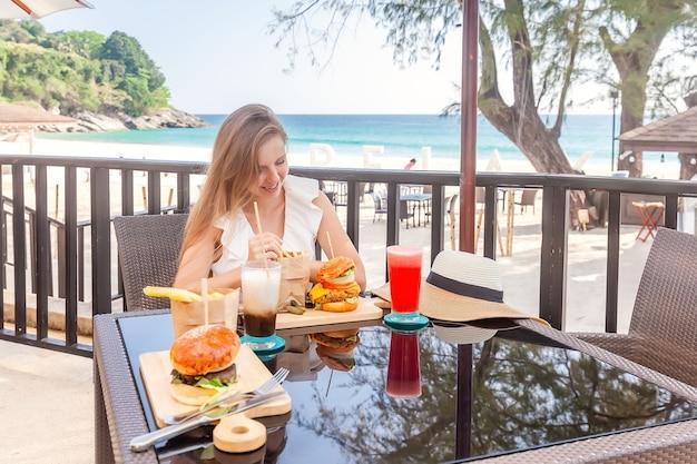 Reisvrouw met fastfoodburgers, koffie en sapdrankjes op terras