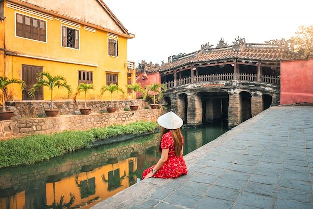 Reisvrouw met japanse behandelde brug, in hoi an, vietnam