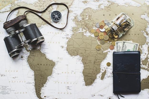 Reizen achtergrond met kaart van de wereld, geld en verrekijkers