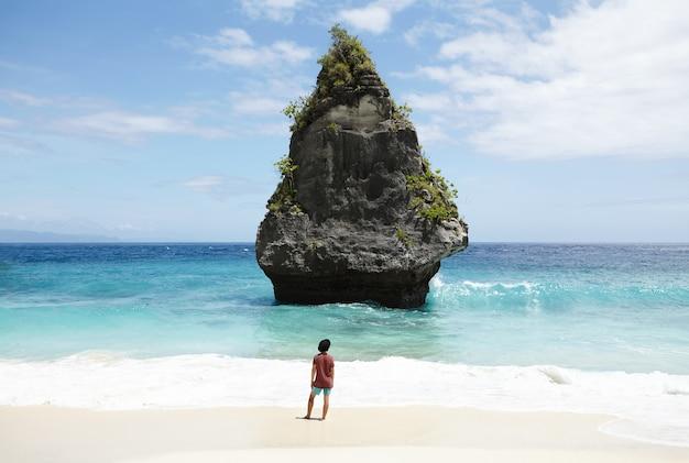 Reizen, avontuur, hobby en vakantie concept. terloops geklede jonge man in zwarte hoed wandelen langs verlaten zandstrand, met uitzicht op turquoise oceaan met stenen eiland met hoge rotsen in het midden