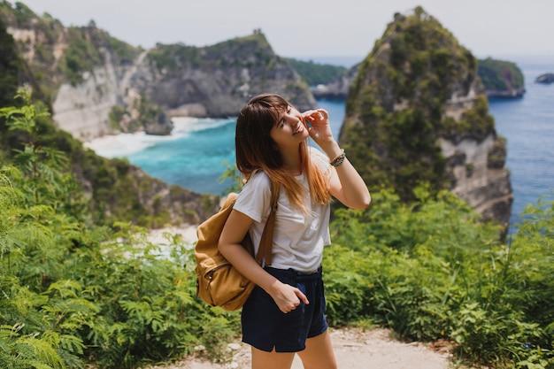 Reizen en avontuur concept. gelukkige vrouw met rugzak die in indonesië op het eiland nusa penida reist.