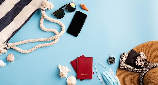 Reizen en avontuur. platliggende reizende objecten met zomerhoed, smartphone, paspoort, zonnebril en kompas op blauwe achtergrond met kopieerruimte