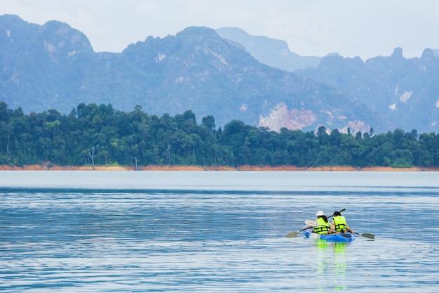 Reizen en huwelijksreis kajakken en kanoën met geliefde. uitzicht op bergen