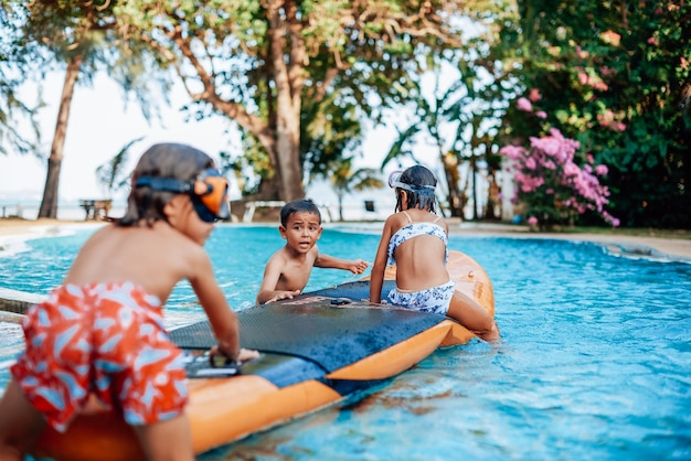 Reizen en recreatie in thailand. drie jeugdkinderen in zwemkleding spelen en vermaken zich samen in het zwembad met boot.