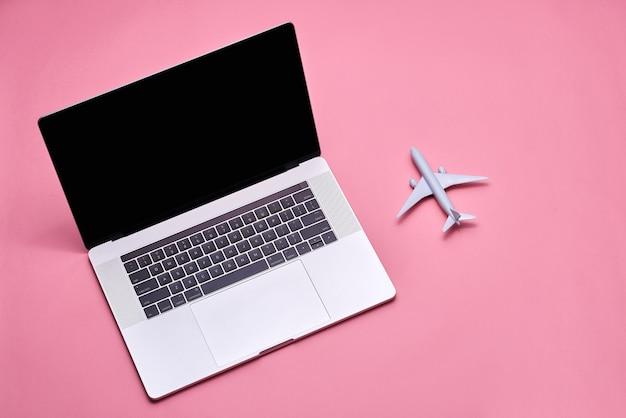 Reizen en schaven concept. vliegtuig speelgoedmodel met laptopcomputer