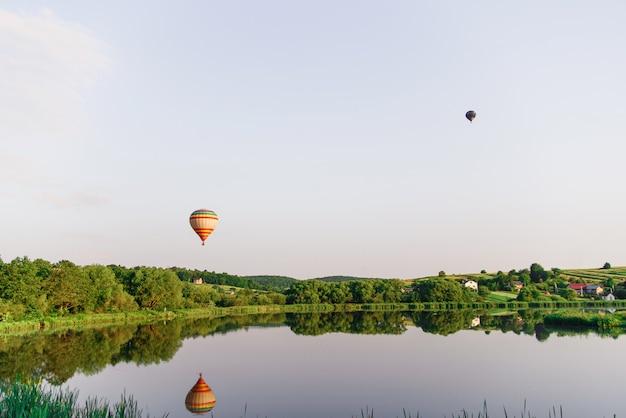 Reizen en sport. twee multi gekleurde hete luchtballons die boven meer in hemel bij zonsopgang vliegen.