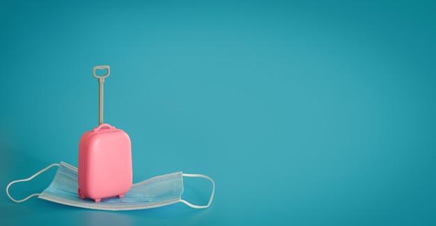 Reizen en vluchten in de tijd van covid-19. mini koffer en medisch masker op de blauwe achtergrond. vrije ruimte, kopieer ruimte. vakantie, vakantie in coronatijden. kleurrijk ontwerp.
