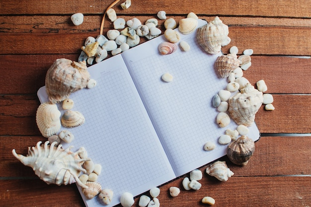 Reizen en vrije tijd, op een houten tafel ligt een notitieboekje naast verspreide schelpen