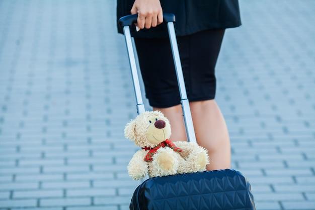 Reizen. het bebouwde jonge toevallige wijfje gaat bij luchthaven bij venster met koffer wachtend op vliegtuig