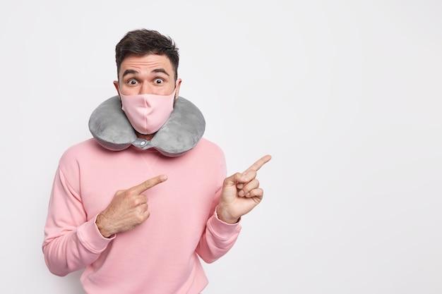Reizen in de tijd van covid 19. verrast vrolijke man reist tijdens quarantainetijd draagt comfortabel reiskussen om nek beschermend masker geeft aan op lege kopieerruimte tegen witte muur