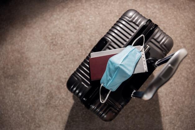 Reizen in het coronavirus-situatieconcept. bovenaanzicht van bagage, paspoort en chirurgisch masker. weg naar bescherming en veiligheid tegen covid-19