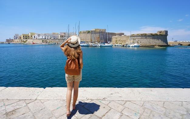 Reizen in italië. achteraanzicht van jonge reiziger vrouw genieten van uitzicht op de oude stad gallipoli met kasteel, italië, europa.