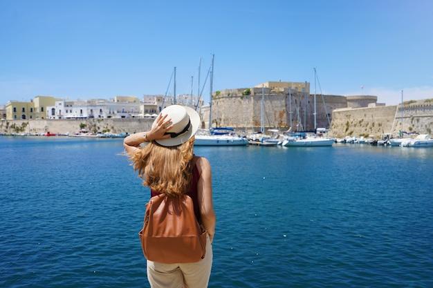 Reizen in italië. achteraanzicht van jonge reiziger vrouw genieten van zeegezicht van gallipoli, italië, europa.