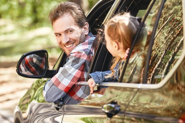 Reizen is leven als vader en dochter die uit het autoraam kijken en glimlachen