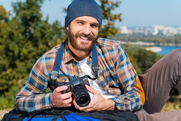 Reizen is onmogelijk zonder camera. knappe jonge man die op de rugzak ligt en camera vasthoudt