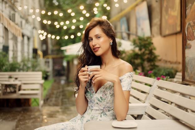 Reizen, koffie, vrije tijd, levensstijl en mensen concept - mooie dame in een restaurant. portret van een mooie jonge vrouw die 's nachts vrolijk is in een restaurant.