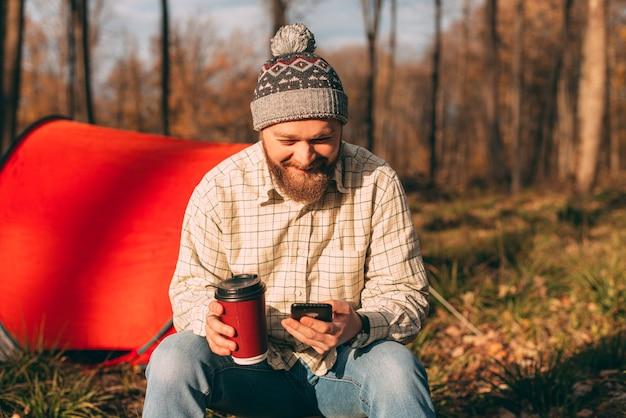 Reizen, mensen en een gezonde levensstijl. foto van een bebaarde man zit in de buurt van tent en met behulp van mobiel