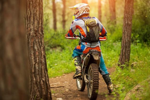 Reizen motorfiets off-road motorrijderuitrusting, kijkt in herfstbos, avontuurconcept, actieve levensstijl, enduro, einde van het seizoen, alleen