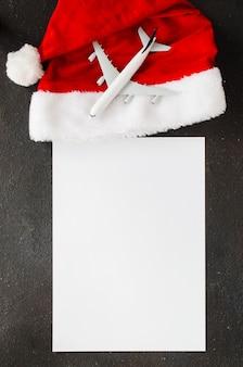 Reizen of kerstreisplanning. blanco papier en speelgoed vliegtuig op kerstmuts.