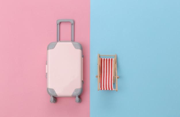 Reizen of strandresort plat leggen. mini plastic reiskoffer, ligstoel op roze blauwe pastelachtergrond. minimale stijl. bovenaanzicht