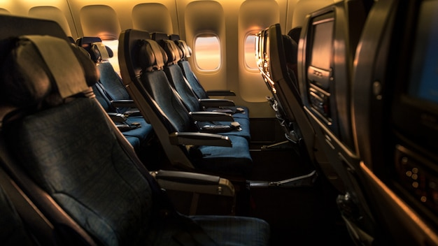 Reizen per vliegtuig. binnen bij vliegtuig lege cabine. zetels met mooi oranje licht van een zonsondergang. prachtig uitzicht op de lucht met de schemering door een vliegtuigraam.