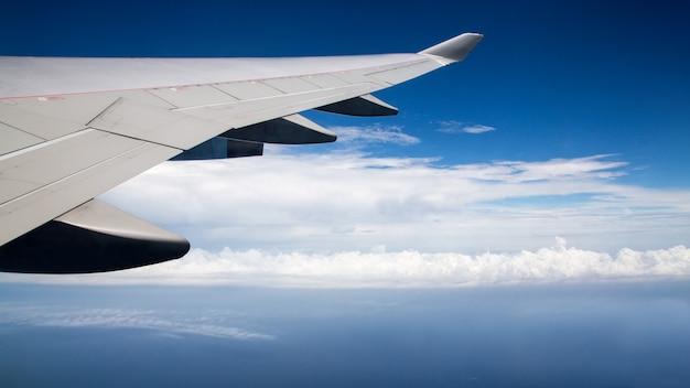 Reizen per vliegtuig. vliegtuigvleugel tijdens vliegreis. mooie lucht en prachtige wolken met lichte zon van bovenaf, gezien door het vliegtuigraam. zicht op reiziger in cabine